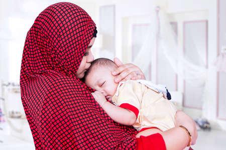 femmes muslim: Une jeune mère portant la mode musulmane et embrasser son bébé dans la chambre à coucher à la maison
