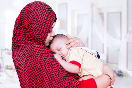 indonesian woman: Young mother wearing muslim fashion and kiss her baby in the bedroom at home