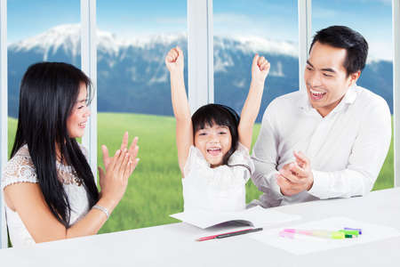 finishing school: Photo of two young parents giving applause on their daughter after finishing school assignment at home