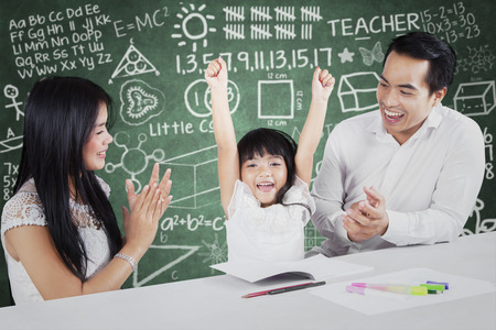 proud: Photo of two proud and happy parents giving applause on their daughter after finishing schoolwork Stock Photo