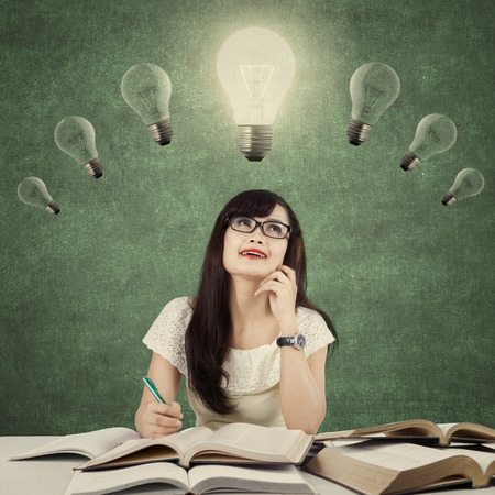 idea bulb: Image of a smart female student doing school assignment and get idea under light bulb