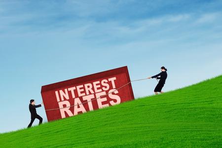 on high: La gente de negocios que tiran de una caja con las tasas de interés en la palabra hasta la colina Foto de archivo