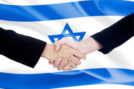 politicians: Two politicians in business suit, shaking hands in front of israel flag background Stock Photo