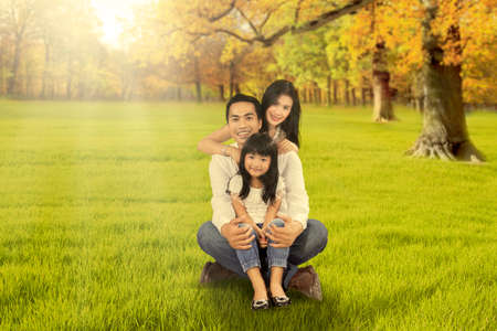 happy family nature: Photo of three member of happy family smiling at the camera while sitting on the grass at autumn park