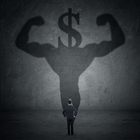 shadow man: Young businessman looking at a shadow of strong athlete with a dollar sign head