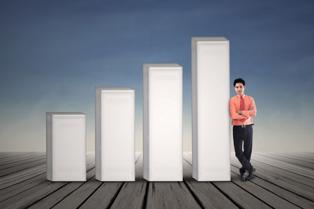 bar graph: Young businessman standing next to growing bar chart on blue sky background