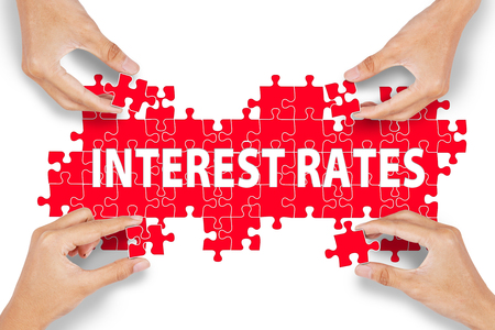 interest rates: Hands with puzzle making INTEREST RATES word isolated on white Stock Photo