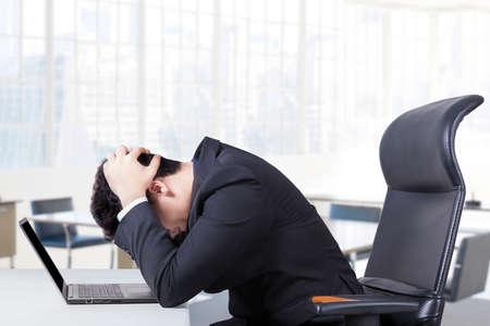 confundido: Empresario estresante sentado en la silla de oficina con un ordenador portátil en la mesa y con la cabeza