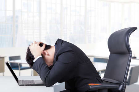 Stressful entrepreneur sitting in the office chair with a laptop on the table and holding his head Stock Photo