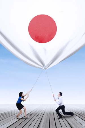 young entrepreneurs: Portrait of two young entrepreneurs work together to bring down a japanese flag