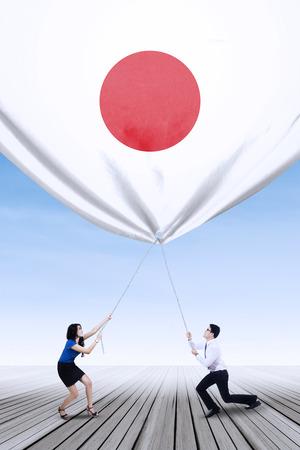 jovenes emprendedores: Retrato de dos jóvenes emprendedores trabajan juntos para derribar una bandera japonesa Foto de archivo