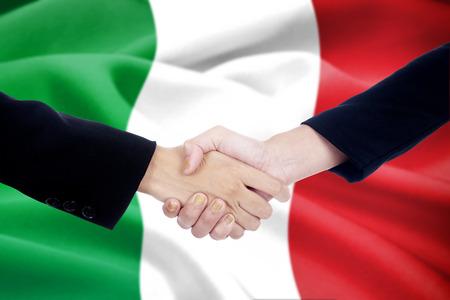 buen trato: Dos empresarios de cierre de negociaci�n con un buen trato y estrechar la mano delante de fondo bandera italiana