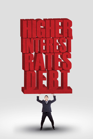 per cent: Businessman lifting HIGHER INTEREST RATES DEBT words isolated over white