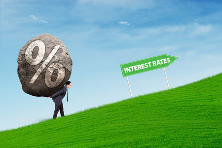 Businessman carries a stone with percentage rates symbol walking uphill following Interes Rates road sign