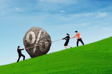 Los hombres de negocios trabajan juntos tratando de conseguir una piedra porcentaje cuesta arriba