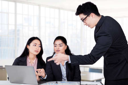 looking at computer: Young caucasian entrepreneur explain business plan with laptop while standing in front of his partners