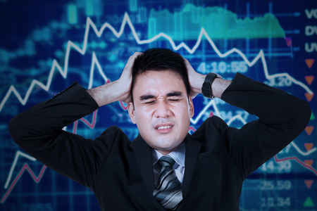 market crash: Young male entrepreneur looks depressed with hands on head and a down stock exchange background