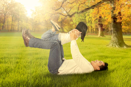 single parent: Photo of happy little girl playing with her dad on the autumn park and lifted by her dad