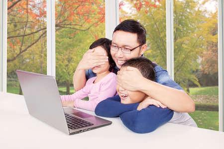 they are watching: Image of young father closing the eyes of his children to avoid they watching adult content Stock Photo