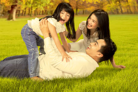 Portrait of happy asian family enjoying holiday by playing together on the autumn park
