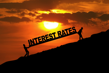 to raise: Silhouette of businessmen carrying Interest Rates word uphill Stock Photo