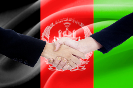 politicians: Two politicians shaking hands in front of afghanistan flag background Stock Photo