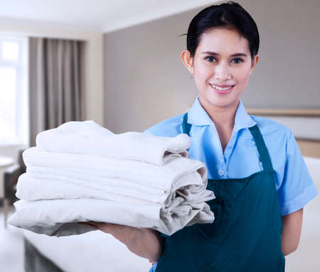 orden y limpieza: Sonriendo jóvenes toallas señora de la limpieza que llevan a cabo en una habitación de hotel Foto de archivo