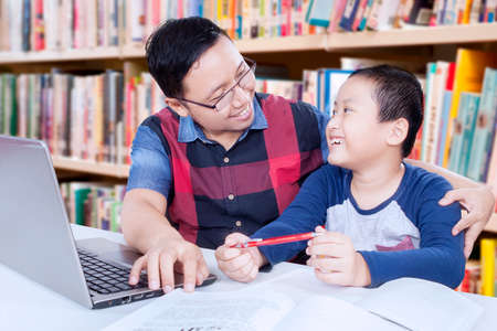 Photo of young asian man talking with a little boy while teaching him in the library