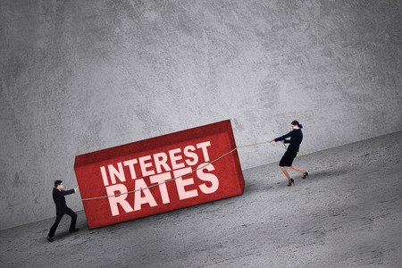 interest rates: Business people trying to get a block with interest rates word on it
