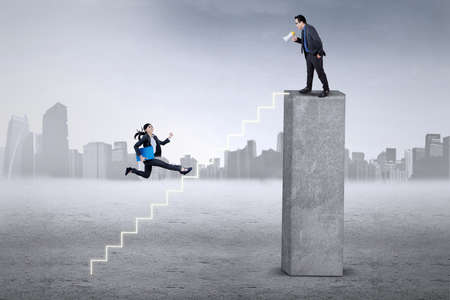 fussy: Young female entrepreneur carrying a folder and hurry stepping the stairs to meet her boss