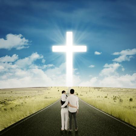 Terug oog van gelukkige familie staande op de snelweg, terwijl kijken naar een kruis op het einde van de weg