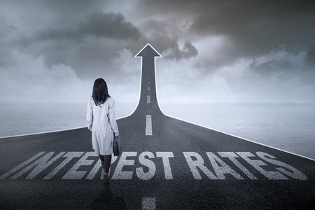 rate: Businesswoman walking on an asphlat road turning into an anscending arrow with interest rates words on it