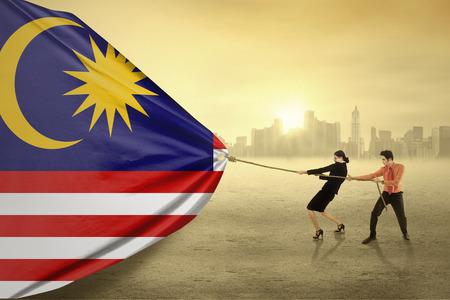 bandera japon: Retrato de dos hombres asiáticos jóvenes que tiran de una bandera de Malasia, dispararon al aire libre