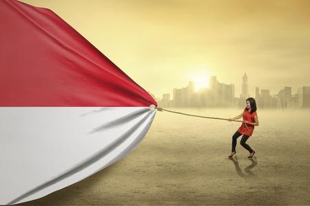 インドネシアの旗を引く若い女性の肖像画の屋外撮影