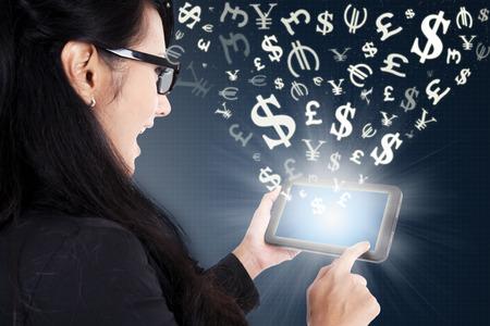 Jeune femme d'affaires prospère à l'aide d'une tablette numérique pour faire de l'argent en ligne