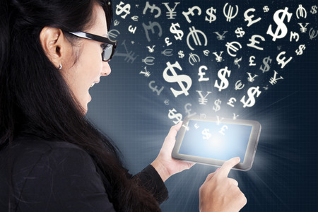 using tablet: Successful young businesswoman using a digital tablet for making money online Stock Photo