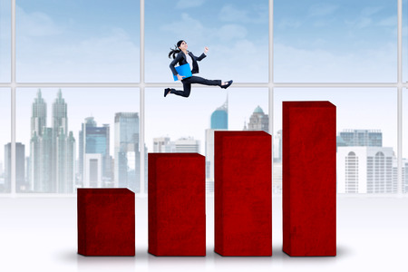 chase: Young business person chase her business target by jumping over business graph Stock Photo