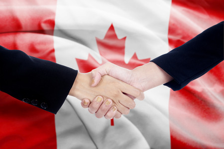 politicians: Two politicians shaking hands in front of canada flag background