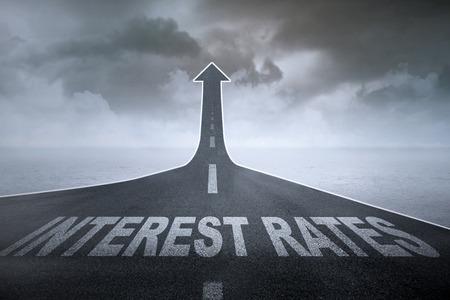 Mayores tasas de interés concepto: Las palabras las tasas de interés en un camino recto que se convierten en la flecha ascendente Foto de archivo