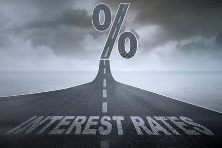 Les mots taux d'intérêt sur une route goudronnée et un signe pour cent au sommet de la rue, symbolisant les taux d'intérêt croissants