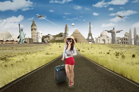 niñas chinas: Turista femenino de pie en la carretera, mientras que el transporte de equipaje con famosos en la parte posterior