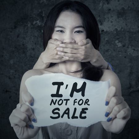 prostitution: Adolescent girl with mouth covered by someone hands, showing a paper with a text of not for sale Stock Photo
