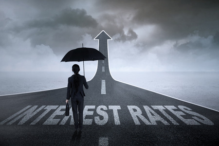 plan view: Businesswoman bringing an umbrella on a asphalt road turning into an ascending arrow with interest rates words on it Stock Photo