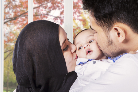 muslim baby: Image of young asian parents kissing their baby cheeks near the window at home