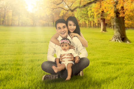 kids hugging: Image of two young happy parents sitting on the autumn field with their daughter