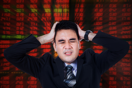 work stress: Photo of male broker looks stressful with hands on head and red stock background Stock Photo