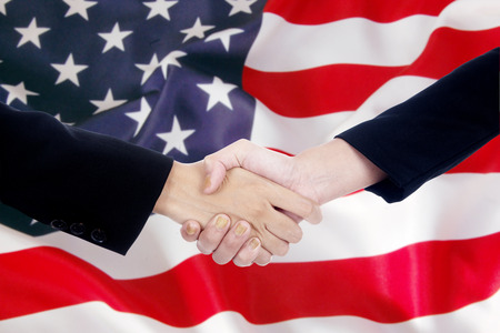 international business agreement: Two people in business suit, shaking hands in front of american flag. Partnership and politics concept