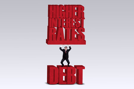 per cent: Businessman lifting HIGHER INTEREST RATES words while standing on the word DEBT isolated over white