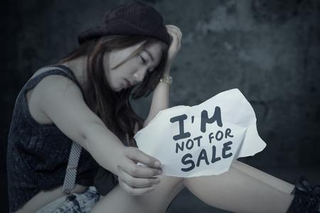 prostituta: Retrato de niña víctima de la trata de personas frustradas, sentado a solas con un documento Foto de archivo