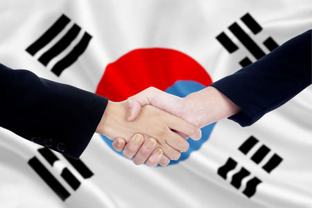 korean flag: Two businesspeople shaking hands in front of south korean flag background Stock Photo